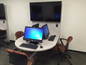Group of three student workstations with large digital display