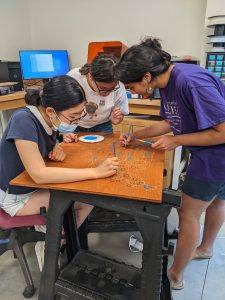 Three students add paint to a wooden map in the Makerspace